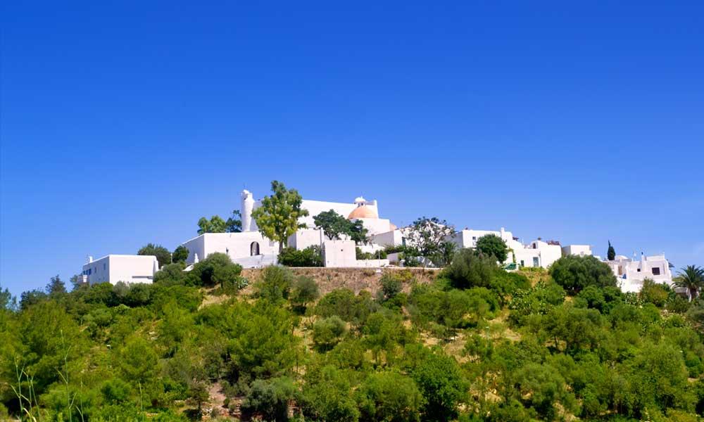 Een heuvel met idyllische witte huisjes in Santa Eulalia op Ibiza