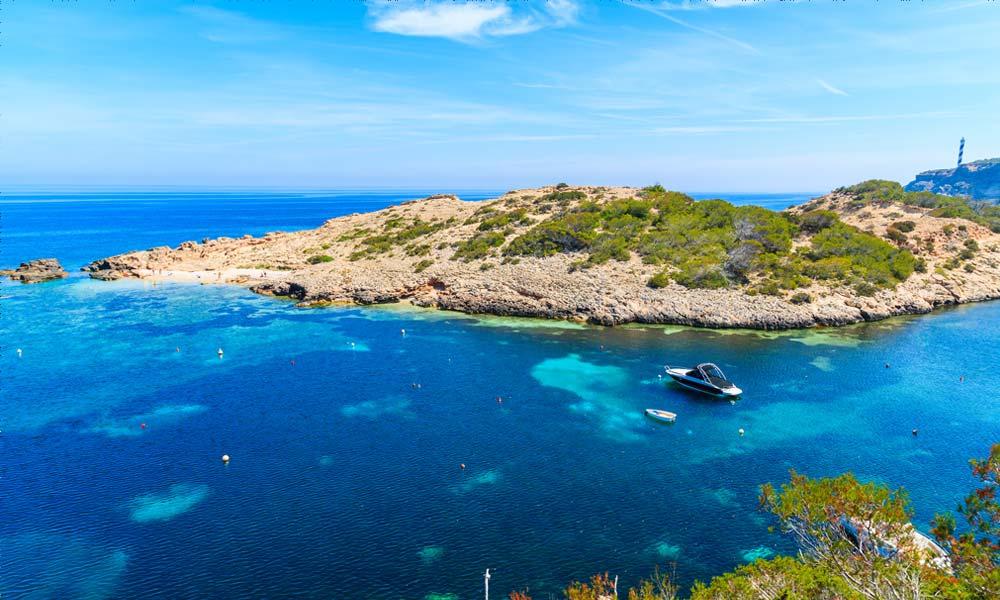 De groene kust met uitzicht op het water en bootjes in de baai van Cala Portinatx op Ibiza